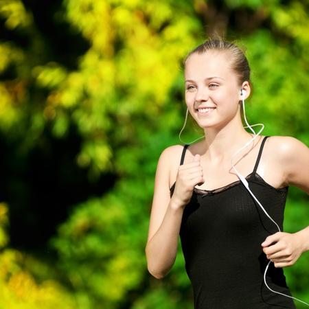 Foto de Beautiful young woman running in green park on sunny summer day - Imagen libre de derechos