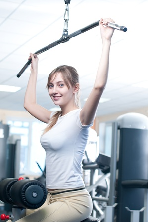 Fitness - powerful casual woman lifting weights in gym club