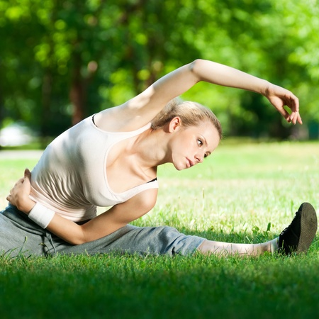 Photo pour Beautiful young woman doing stretching exercise on green grass at park. Yoga - image libre de droit
