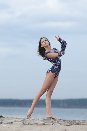 young professional gymnast woman dance - outdoor sand beach