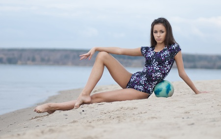 young professional gymnast woman dance with ball - outdoor sand beach