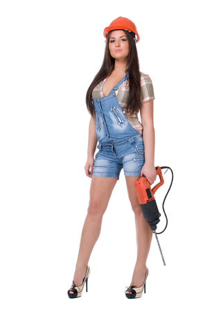 Young sexy female dressed in jeans and orange helmet holding hammer  electric drill. White isolated