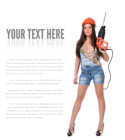 Young female dressed in jeans and orange helmet holding hammer electric drill on White isolated background.