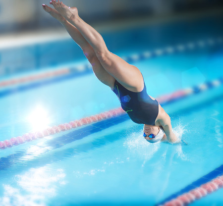 Photo pour Portrait of a female swimmer, that jumping and diving into indoor sport swimming pool. Sporty woman. - image libre de droit