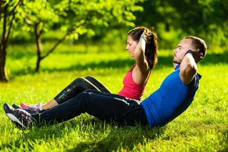 Man and woman exercising at the city park. Beautiful young multiracial couple. Sit ups fitness couple exercising outside in grass. Fit happy people working out outdoor.