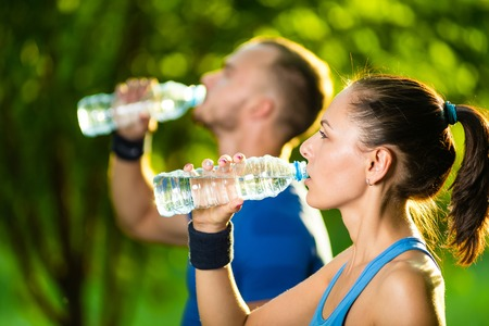 Photo pour Man and woman drinking water from bottle after fitness sport exercise. Smiling couple with bottles of cold drink outdoors - image libre de droit