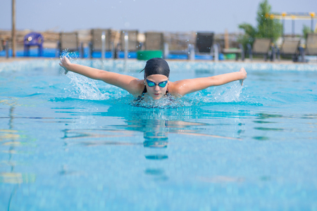 Photo pour Young girl in goggles and cap swimming butterfly stroke style in the blue water pool - image libre de droit
