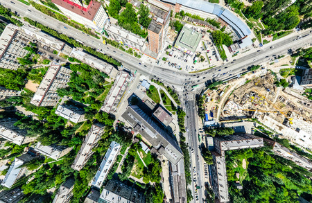 Photo pour Aerial city view with crossroads and roads, houses, buildings, parks and parking lots. Sunny summer panoramic image - image libre de droit