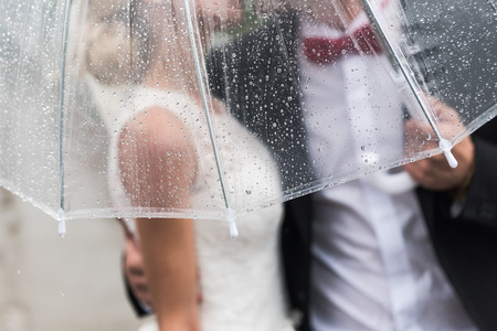 the bride and groom in the rain are covered with a transparent umbrella, rain dropsの写真素材