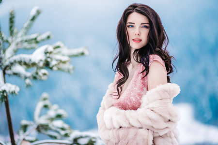 Foto de girl with chestnut hair, blue eyes and a pink dress on the background of the winter mountains - Imagen libre de derechos