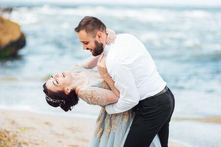 Foto für same couple with a bride in a blue dress walk along the ocean shore - Lizenzfreies Bild