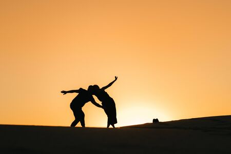Photo pour silhouettes of a happy young couple guy and girl on a background of orange sunset in the sand desert - image libre de droit
