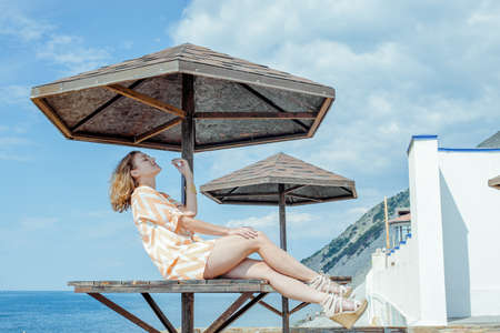 Photo for A young woman in a summer dress on the black sea embankment - Royalty Free Image