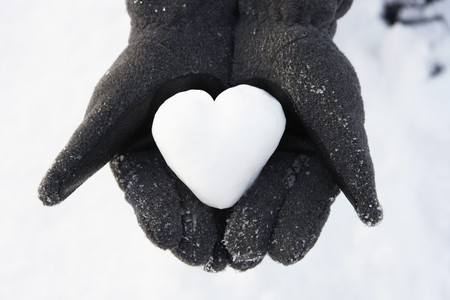 Photo pour Close Up Of Hands Holding Heart Made Out Of Snow - image libre de droit