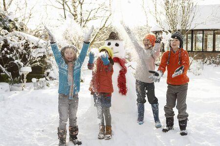 Photo pour Children Building Snowman In Garden - image libre de droit