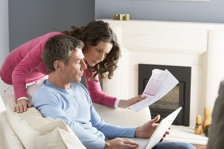Couple Using Laptop And Discussing Household Bills Sitting On Sofa At Home