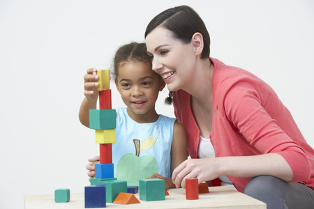 Foto de Teacher And Pre-School Pupil Playing With Wooden Blocks - Imagen libre de derechos