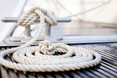 Close-up of mooring rope with a knotted end tied around a cleat on a wooden pier.