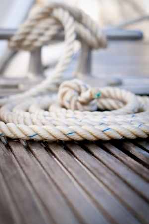 Close-up of a mooring rope with a knotted end on a wooden pier.