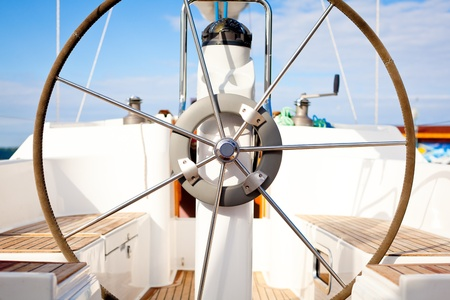 A steering wheel on a boat with empty seats.