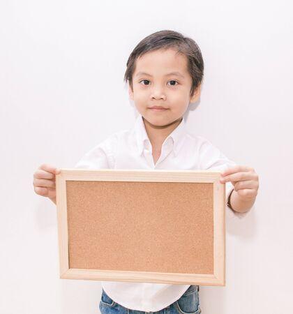 portrait of a little boy holding a board