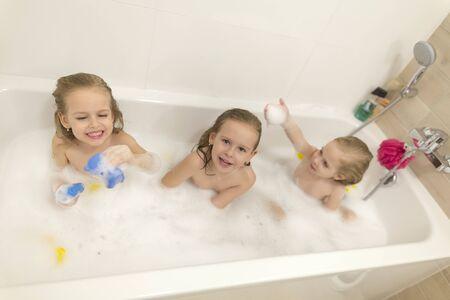 Photo pour Happy children girls are bathing in a bath with foam and bubbles. - image libre de droit