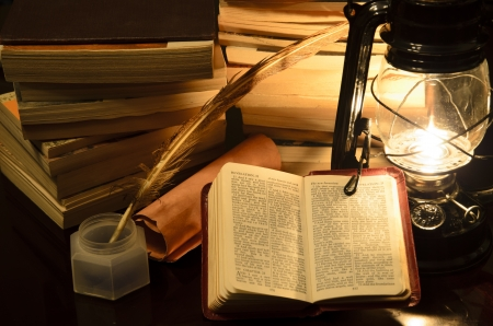 a bible surrunded by books in a lamp light