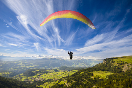 Foto de Paraglider flying over mountains in summer day - Imagen libre de derechos