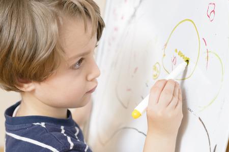Cute boy drawing at kindergarten on a white board