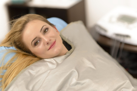 Photo for Beautiful young woman getting thermal blanket treatment at beauty salon - Royalty Free Image