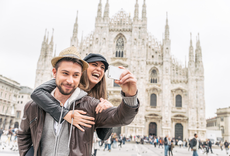 Happy tourists taking a self portrait with phone in front of Duomo cathedral,Milan - Couple travelling in Italy