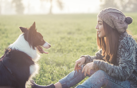 Young woman playing with her border collie dog. concept aout animals and people