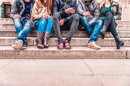 Photo pour Group of people sitting on a staircase outdoors, close up on low section body - Multiracial friends talking and having fun on a meeting outdoors - image libre de droit