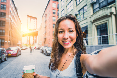 Photo pour Pretty mixed race woman taking a selfie in New York, Brooklyn Bridge in the background - Beautiful girl walking on the streets of NY and photographing some landmarks - image libre de droit