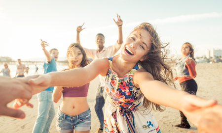 Group of friends having fun and dancing on the beach. Spring break party on the beach