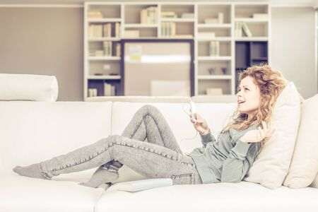 Beautiful woman listening music on portable device in the living room - Young pretty girl singing and relaxing while lying down on the sofa