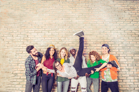 Photo pour Group portrait of multi-ethnic boys and girls with colorful fashionable clothes holding friend in hands and posing on a brick wall - Urban style people having fun, studio shot - Concepts about youth  and togetherness - image libre de droit
