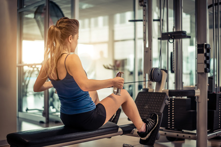 Woman training her back and shoulder with weight machine in a gym