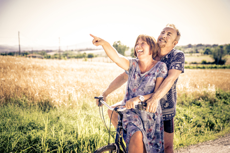 Photo pour Middle age couple going for a ride with the bicycle in the countryside - Senior couple having fun outdoors - image libre de droit