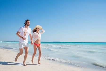 Photo for Couple strolling at the beach and smiling - Young adults enjoying summer holidays on a tropical island - Royalty Free Image