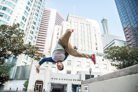 Photo for Parkour man doing tricks on the street - Free runner training his acrobatic port outdoors - Royalty Free Image