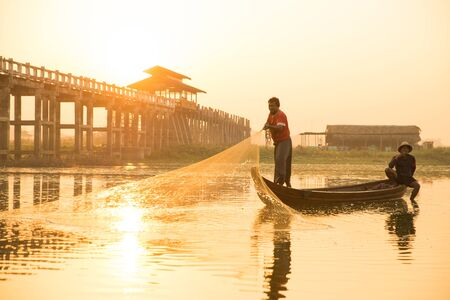 Photo pour Myanmar fisherman throwing fishing net at lake near U Bein Bridge in Mandalay, Myanmar. - image libre de droit