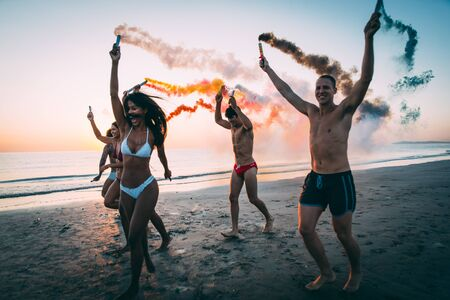 Photo pour Group of friends having fun running on the beach with smoke bombs - image libre de droit