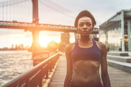 Photo for Athlete woman training in the morning at sunrise in New york city, Brooklyn in the background - Royalty Free Image