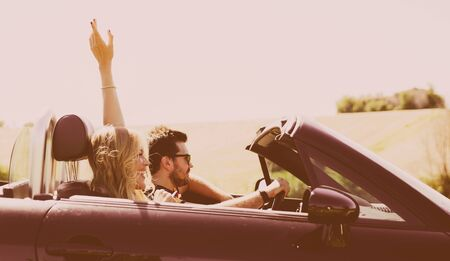 Photo for Couple driving on a convertible car and having fun - Royalty Free Image