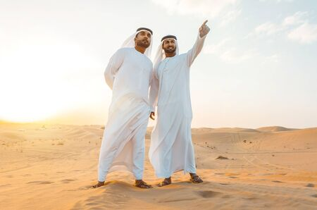 Photo for Two business men wearing traditional uae white kandura spending time in the desert of Dubai - Royalty Free Image