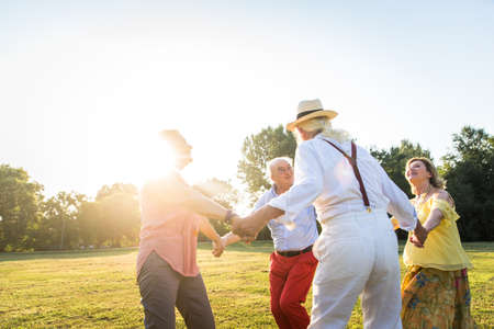 Photo pour Group of youthful seniors having fun outdoors - Four pensioners bonding outdoors, concepts about lifestyle and elderly - image libre de droit