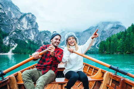 Photo for Mountain stories. Happy couple on a wanderlust vacation. Boyfriend and girlfriend spending time together at the lake. Storytelling concept about lifestyle and winter travels - Royalty Free Image