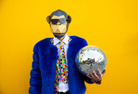 Photo pour Happy man with funny low poly mask on colored background - Creative conceptual idea for advertising, adult with low-poly origami paper mask doing funny poses - image libre de droit