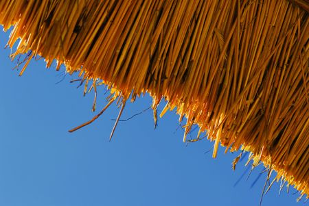 A thatched roof pattern against blue sky